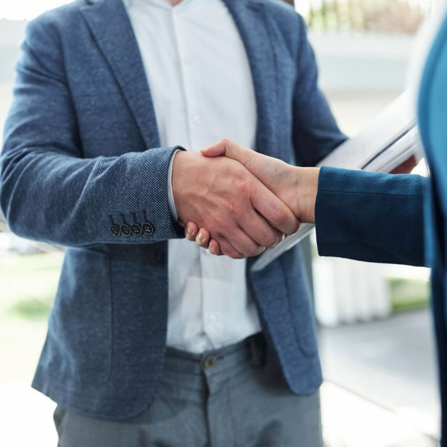 Cropped image of business people shaking hands and confirming deal