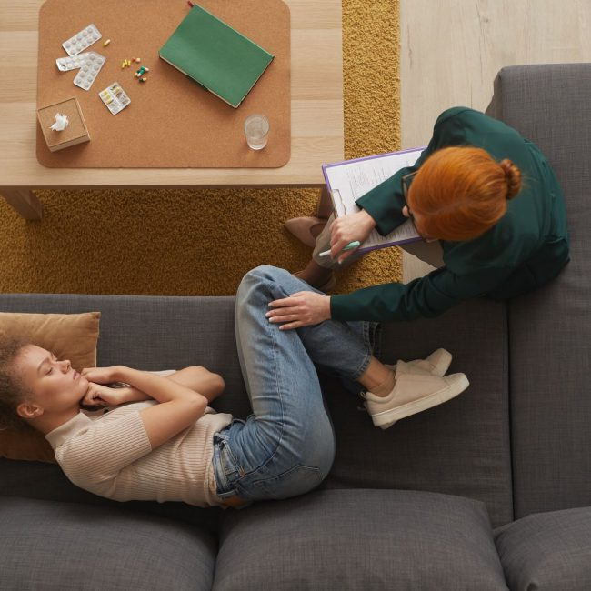 High angle view of young woman lying on sofa in depression while psychologist talking to her at office