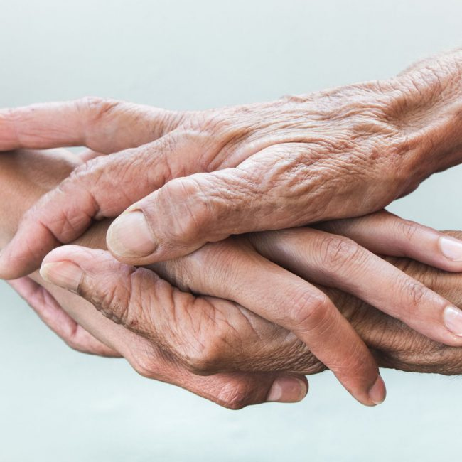 hands-of-young-adults-and-older-women-on-a-light-b-DCDSRSC
